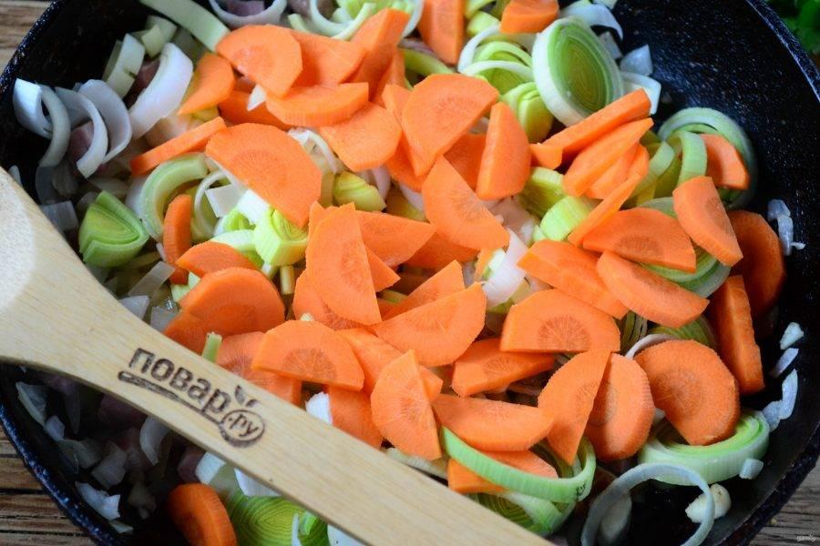 Затем отправьте в сковороду порезанную полукольцами морковь (толщина 3-4 мм) и измельченный лук-порей. Подержите на среднем огне 5-7 минут, чтобы овощи прогрелись и начали размягчаться.