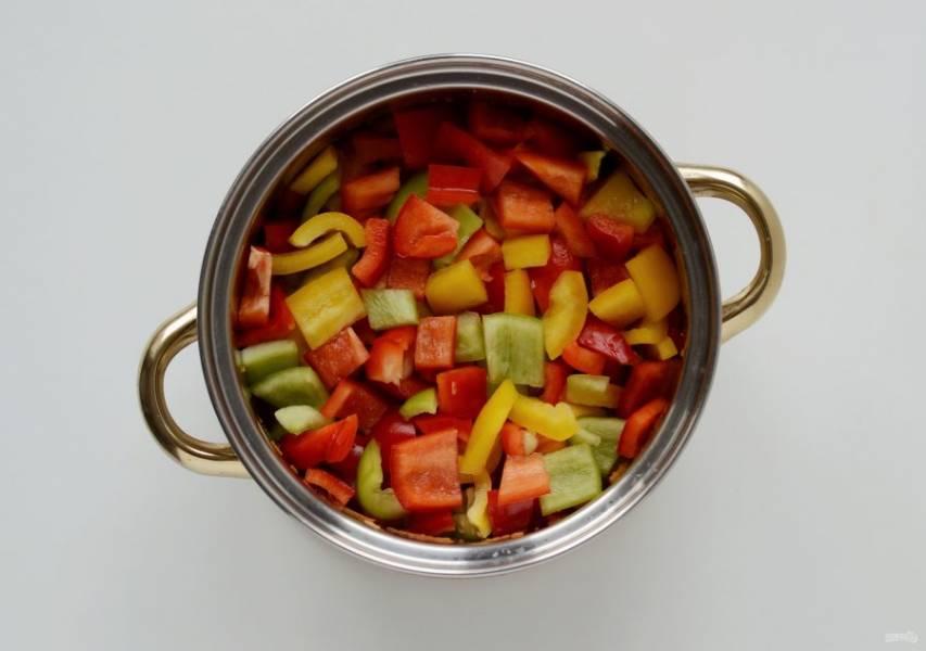 Болгарский перец помойте, удалите хвостики и семена. Нарежьте кубиками, переложите в кастрюлю и тушите ещё 10 минут.