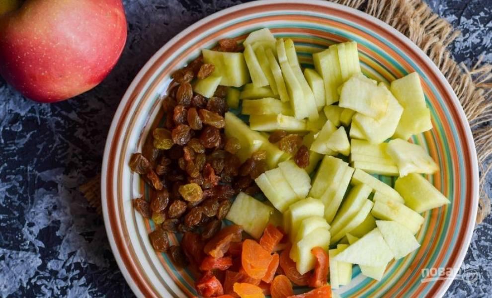 Промойте изюм и курагу, замочите их в горячей воде на пятнадцать минут. Затем помойте и почистите яблоки, удалите серединку с семенами, нарежьте яблоки небольшими кусочками.
