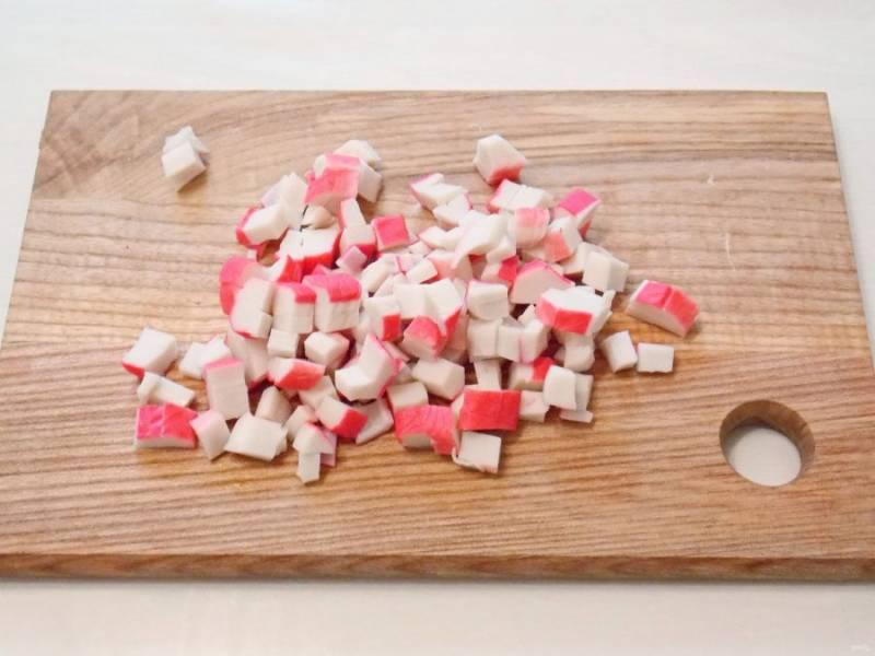Размороженные крабовые палочки очистите от пленки и порежьте кубиком.