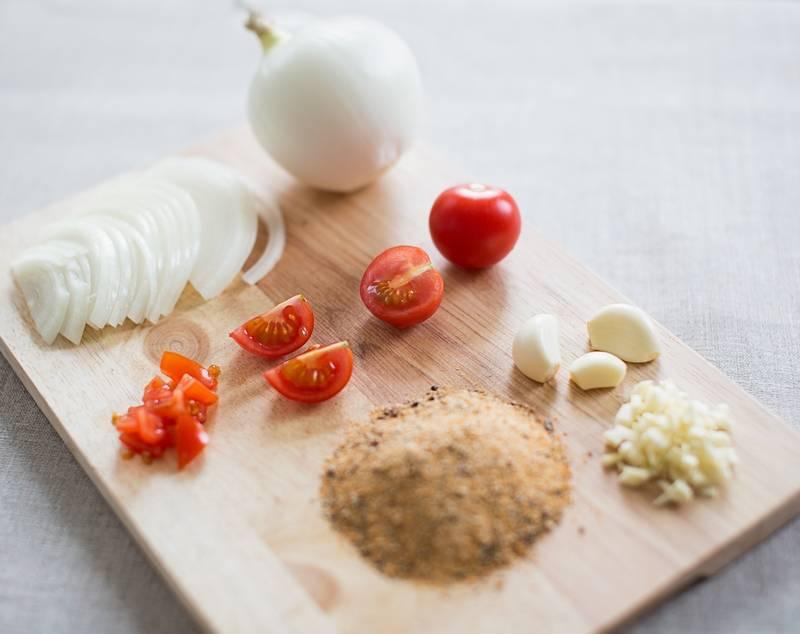Мелко нарезаем помидоры и отправляем к мясу. Кстати, помидоры можно измельчить с помощью блендера или комбаина. Помидорный сок сделает мясо сочнее. Далее измельчаем чеснок, нарезаем полукольцами лук и добавляем все к мясу. Чесночно-луковый сок добавит курице приятный аромат и вкус, а также сделает мясо еще мягче.