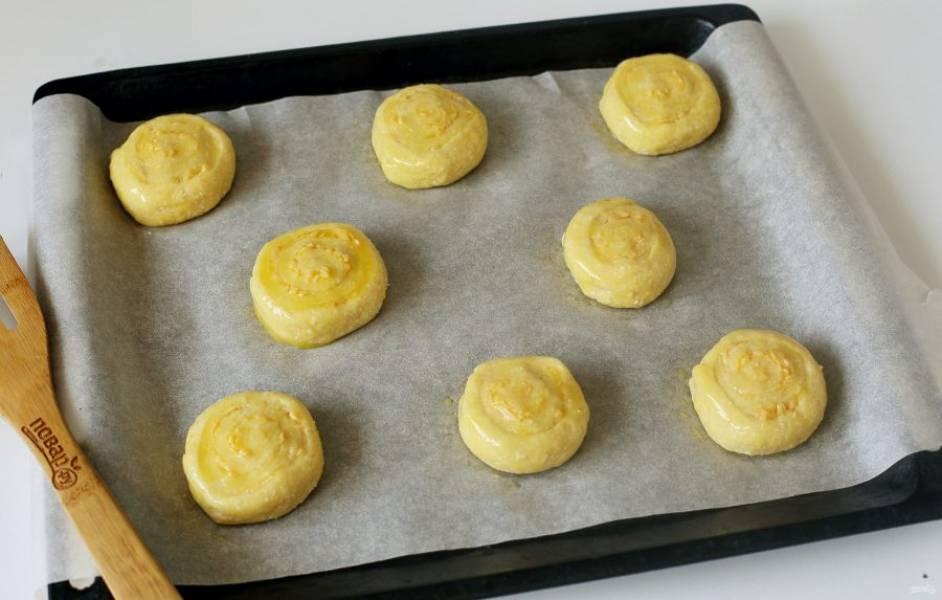 Переложите кусочки срезом вниз, на застеленный пергаментом противень. Верх смажьте яичным желтком и выпекайте изделия в духовке при температуре 190 градусов около 20 минут.