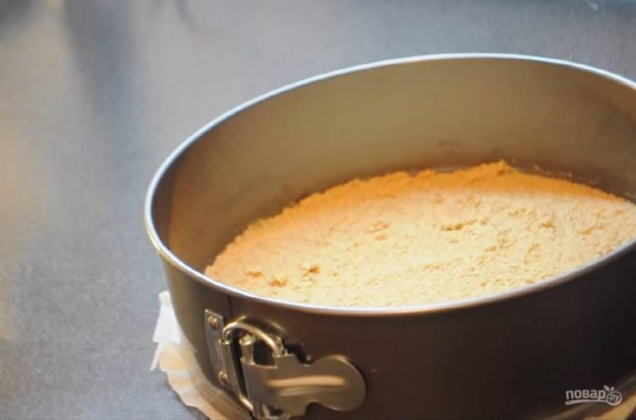 2. Тщательно перемешайте вилкой размягченное сливочное масло с крошкой до однородного состояния. Форму для торта застелите пергаментой бумагой и равномерно распределите на ней печенье. Отправьте в холодильник на 10-20 минут.