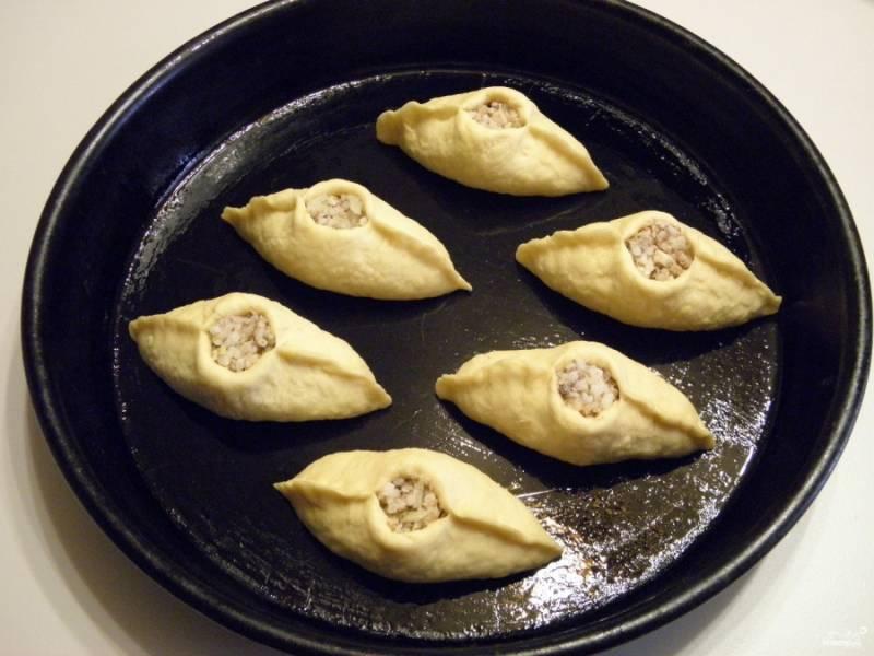 Смажьте противень растительным маслом. Выложите на него пирожки, оставьте их на 20 минут для расстойки. Если хотите получить красивый глянцевый вид, смажьте пирожки яйцом перед выпечкой.
