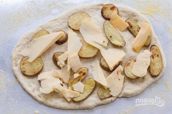 Здесь я использую оставшуюся от ужина отваренную, а затем обжаренную до золотистости картошку. Также ее можно просто запечь в духовке. Выложите картошку на тесто. Сверху уложите крупные кусочки сыра.