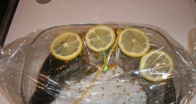 3. Теперь противень или форму смажем маслом, выкладываем рыбу, украшаем кружками лимона. Помещаем вместе с формой в пакет. Связываем края и делаем отверстия в верхней части пакета. Ставим противень с рыбой в рукаве в холодную духовку и затем включаем.