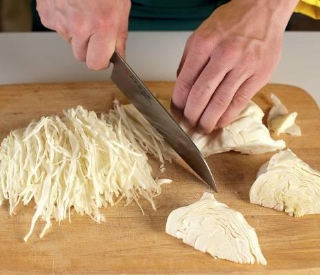 1. Очистите капусту от верхних листьев и нарежьте на 4-6 частей в зависимости от размера. Затем острым ножом нашинкуйте и выложите в глубокую мисочку. При желании можно натереть капусту на шинковке, однако не слишком мелко, чтобы маринованная капуста с клюквой в домашних условиях оставалась хрустящей.