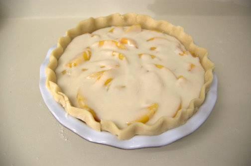 5. Вылить сметанный крем сверху персиков и отправить форму в разогретую духовку минут на 20.