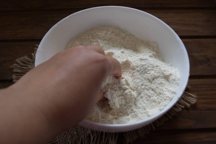 Смешайте муку с маслом. Масло должно быть холодным. Очень быстро смешайте муку с маслом до состояния крошки. Чем дольше масло контактирует с руками, тем менее хрустящим получится печенье.