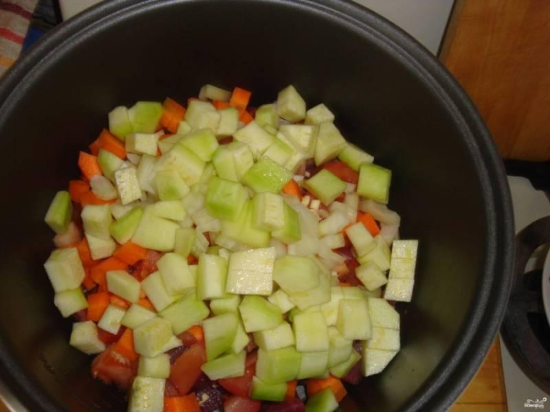 2.Порежьте помидоры на мелкие кусочки. Добавьте их в емкость. Очистите морковь. Порежьте её на небольшие кусочки. Добавьте морковь к мясу. Измельчите мелко чеснок. Добавьте его в емкость к продуктам. Очистите лук от кожуры. Порежьте его на небольшие кусочки. Сложите лук в емкость мультиварки. Очистите кабачок. Порежьте и его на небольшие кусочки. Добавьте к мясу и овощам.