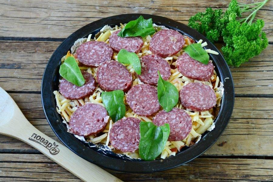 Толстым слоем выложите натертый на крупной терке сыр, сверху разложите тонкие кружочки салями или пепперони и листики базилика или шпината.