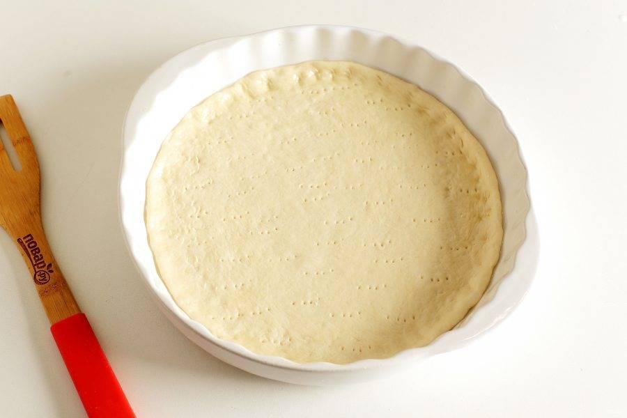 Разделите тесто на две части. Вторую часть можно заморозить или испечь другую пиццу с любой начинкой на выбор. Форму смажьте маслом. Тесто раскатайте по размеру формы (у меня 27 см. в диаметре) на присыпанной мукой поверхности, аккуратно перенесите и сформируйте небольшие бортики. Наколите тесто вилкой.