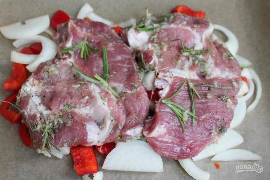 Лук и болгарский перец нарезаем кусочками и выкладываем на противень. Сверху кладем мясо, отправляем в духовку на 45-60 минут. Готовим при температуре 200 градусов.