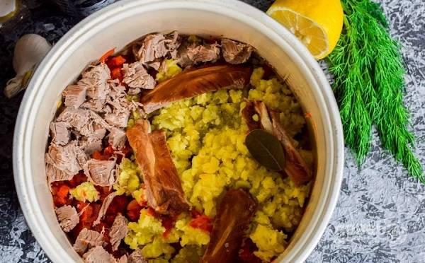 7. Картофель разомните в пюре и добавьте в чашу. Туда же выложите ребрышки и нарезанную говядину. Аккуратно залейте бульоном. Посолите, добавьте специи.