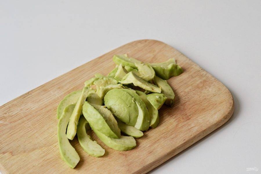 Авокадо очистите от кожуры, удалите косточку и нарежьте ломтиками.