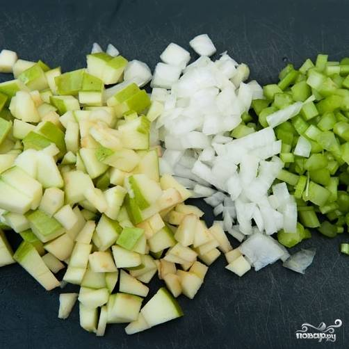 2. Пока курица тушиться, приготовьте овощи. Луковицу очистите и нарежьте мелкими кубиками, сельдерей измельчите. Яблоко очистите от семян и также измельчите.
