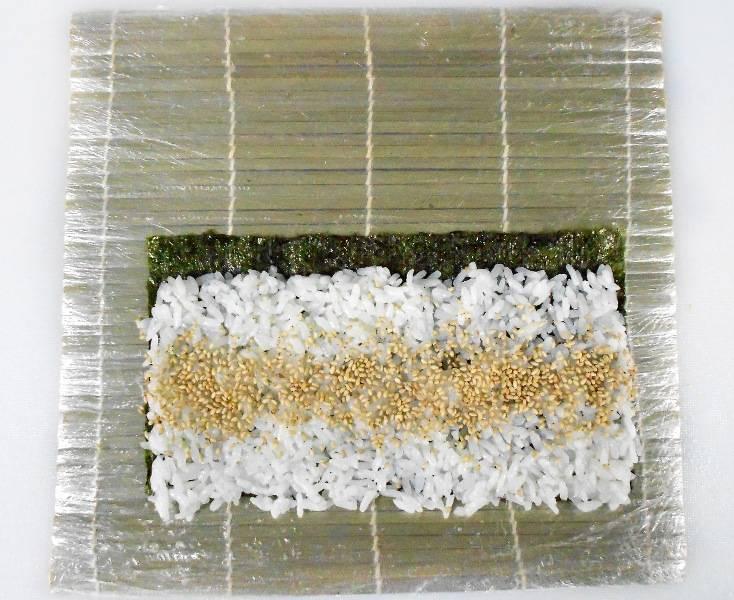Распределяем его равномерно по всему периметру, так чтобы он не доходил до одного края нории на 1 см. Теперь посередине риса делаем небольшую полоску из зерен кунжута.