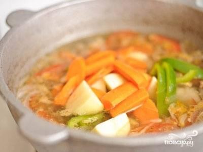 Когда мясо готово, добавить лук, картофель, морковь. Варить 20 минут. Затем добавить перец, помидоры, специи. Варить еще 15 минут.