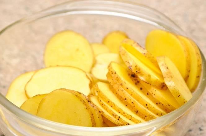"""1. Картофель хорошенько промойте щеточкой и нарежьте тонкими ломтиками при помощи специальной терки или в комбайне, используя насадку """"Мандолина""""."""