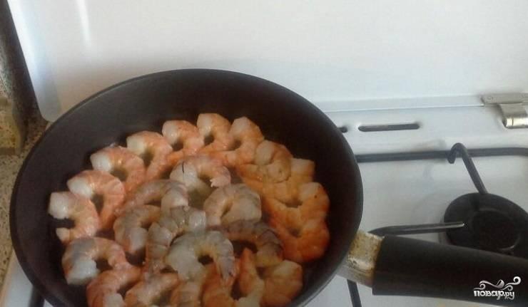 2. Разморозьте креветки. Очистите их от панциря. Подготовьте сковородку: разогрейте и влейте в нее растительное масло. Креветки выкладывайте в масло, когда оно будет хорошо прогрето. Затем обжарьте их с каждой стороны. Слегка поперчите, добавьте чеснок (зависит от вашего вкуса).