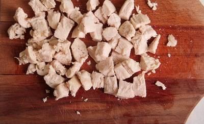 Тем временем, нарезаем кусочками куриное филе и добавляем в кастрюлю.