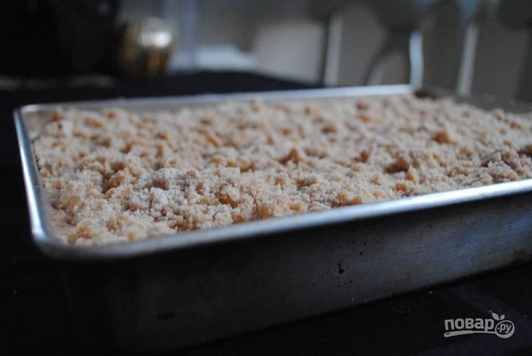 5. Сверху распределите оставшееся тесто. Его можно натереть на терке или покрошить произвольными кусочками. Отправьте противень в духовку.