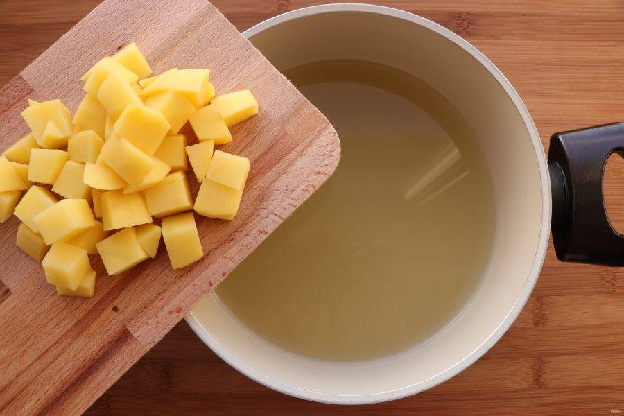 Картофель нарежьте кубиками и опустите в кипящий бульон. Варите 5 минут.