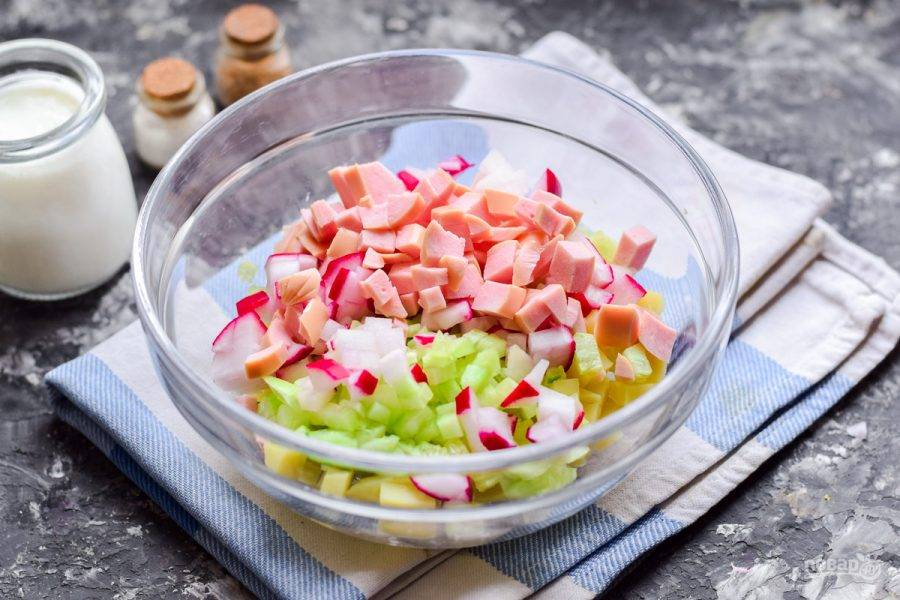 Нарежьте кубиками колбасу, добавьте в овощи.