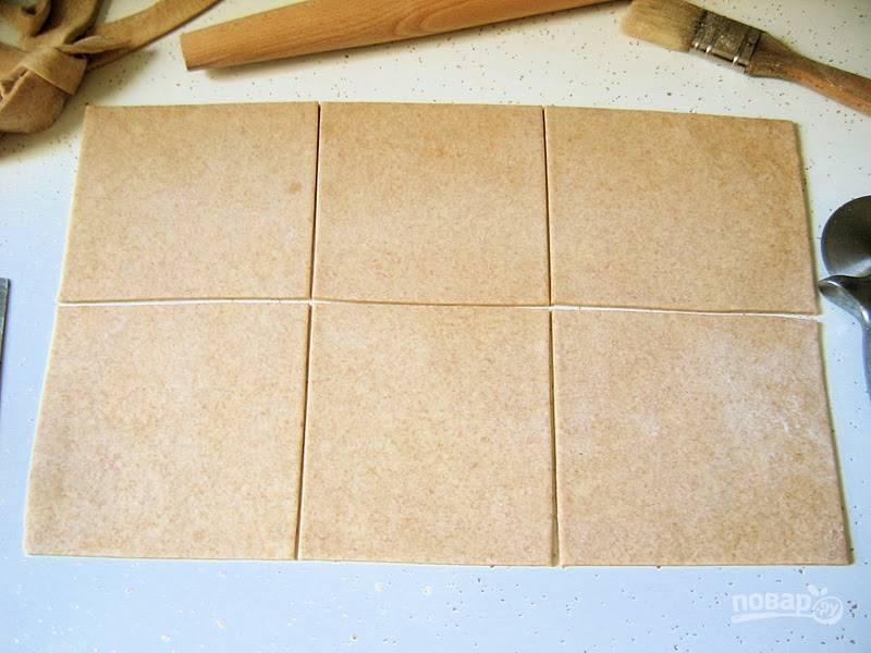 Разморозьте тесто. Выложите его на поверхность и разделите на равные квадраты для слоек.