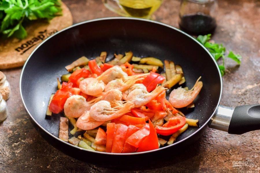 Добавьте к баклажанам помидоры, перец, креветки и измельченный чеснок.