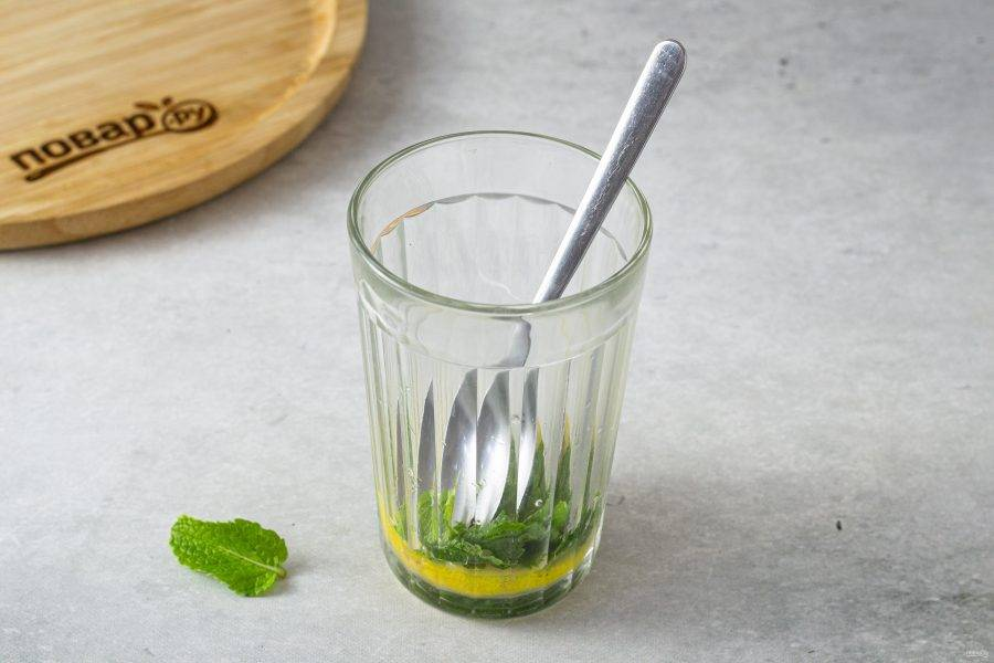 Выложите в высокий стакан лимон и мяту. Разомните, чтобы они пустили сок.