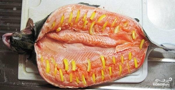 Рыбу почистить, выпотрошить (голову и хвост не удалять!), вымыть. Обсушить бумажными салфетками. Сделать небольшие, но довольно глубокие надрезы изнутри и вложить в них кусочки лимона.