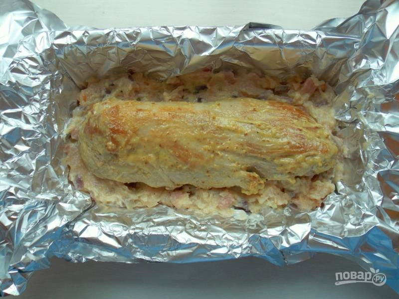 Добавьте к фаршу сливки, яйцо, соль, перец и обжаренные овощи с беконом. Перемешайте и положите половину в форму застеленную фольгой. На верх положите вырезку посоленную и обмазанную горчицей.