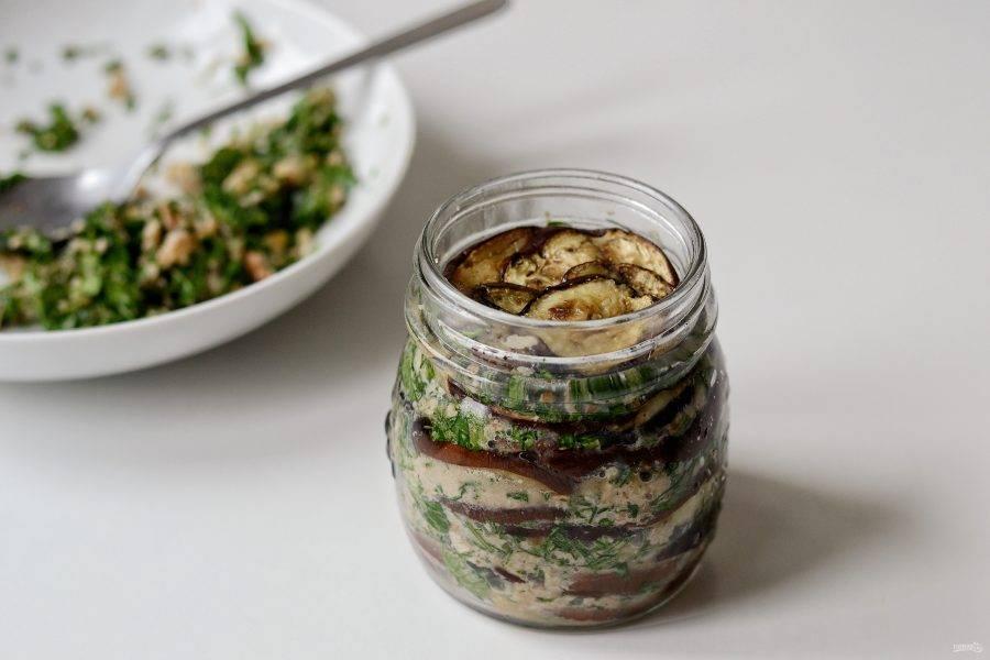 Подготовьте чистые банки. Выложите слоями кружочки баклажанов и ореховую начинку.