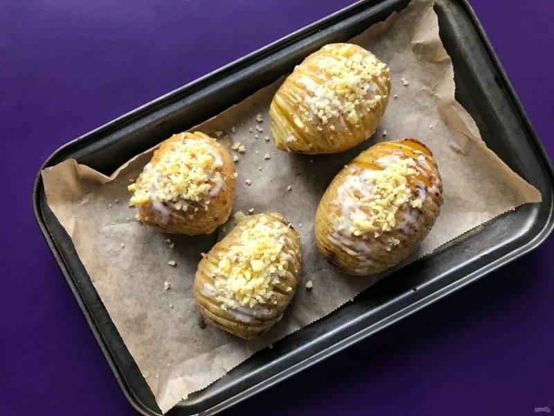 За 5 минут до готовности посыпьте картофель тертым сыром и продолжайте запекать.