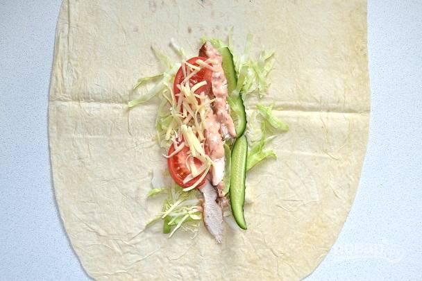 На лист лаваша выложите курицу, соус, овощи и сыр.