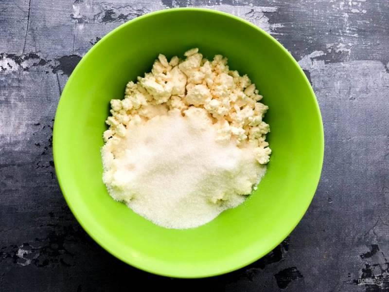 Творог выложите в глубокую тарелку, добавьте к нему сахар и хорошо разотрите вилкой.