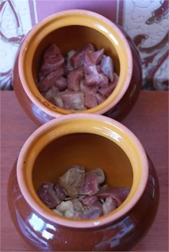 1. Чеснок измельчаем и делим на две части. Одну часть распределяем по дну горшочков, другую оставим на потом. Затем - слой мяса. Солим и перчим.