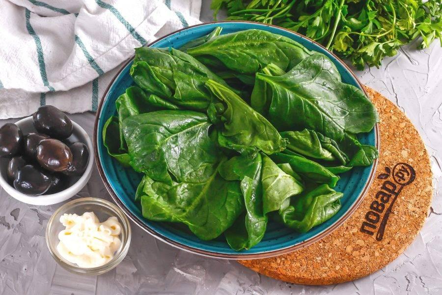Срежьте с пучка шпината стебли, промойте его в воде и разберите на листья. Стряхните с них лишнюю влагу и выложите на тарелку.
