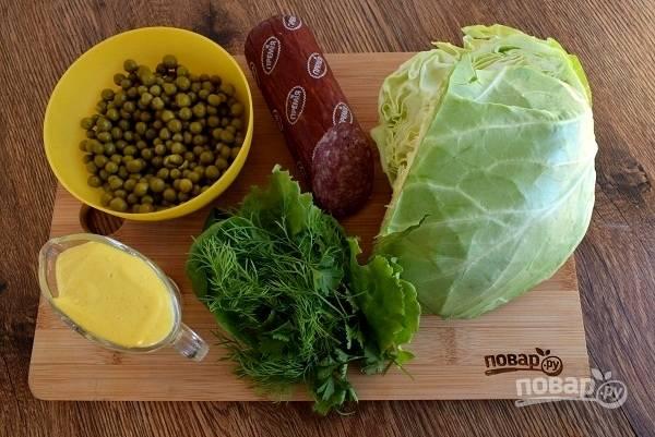 Подготовьте необходимые продукты. С колбасы снимите защитную оболочку. Капусту и зелень промойте под прохладной водой.