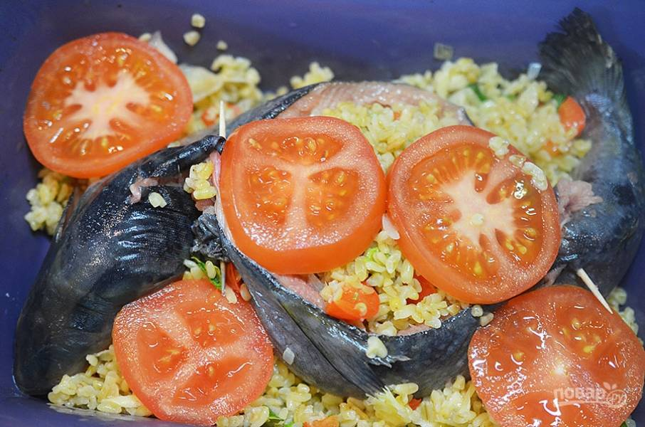 9. Выложите в форму. Если булгур остался, положите его вокруг рыбы. Сверху выложите нарезанный кружками помидор.