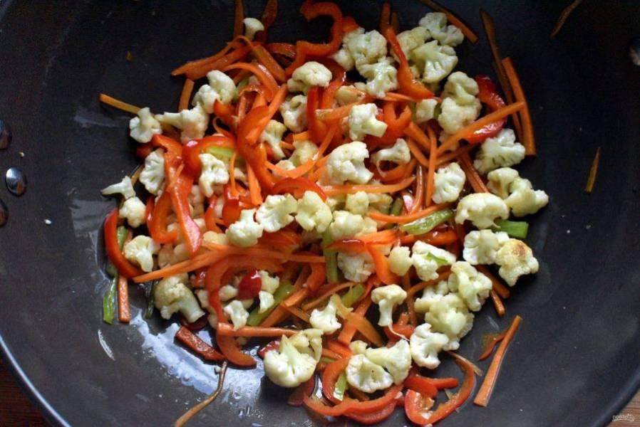 Разогрейте в воке масло и обжарьте капусту пару минут, постоянно помешивая. Затем добавьте морковь и перец. Жарьте еще пару минут, так же помешивая.
