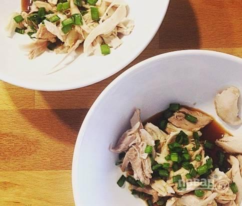 Возьмите тарелки для подачи, разложите в них отварное куриное мясо. Налейте в каждую по десять грамм соевого соуса. Добавьте немного рубленого зеленого лука.