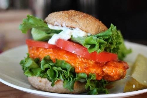 4. Жареные грудки выберите на тарелку, а в сковороду добавьте сливочное масло и томатный соус, перемешайте и прогрейте. Когда масло растопится, обваляйте обжаренные грудки в соусе. Затем сразу же формируйте бутерброд с курицей. На булочку выложите филе, затем салатный лист, пару ломтиков помидора, сверху смажьте соусом. Закройте второй частью булочки и подавайте. Приятного аппетита!