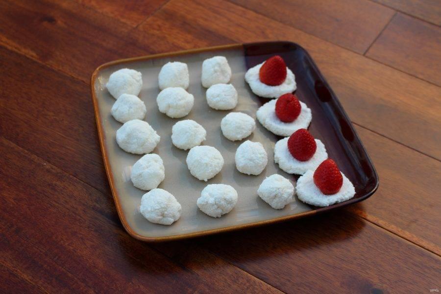 Теперь сделайте небольшие лепёшки из творога. В центр выложите промытую клубнику, оберните её белой массой.