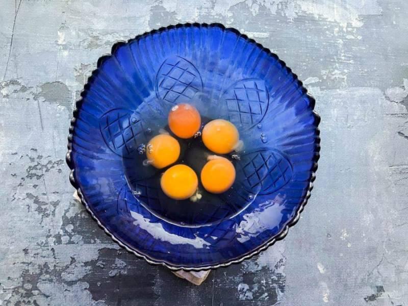 В глубокую емкость вбейте яйца.