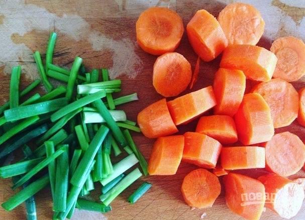 Вымойте часть зеленого лука и морковь. Очистите ее. Нарежьте лук и морковь крупными кусочками.