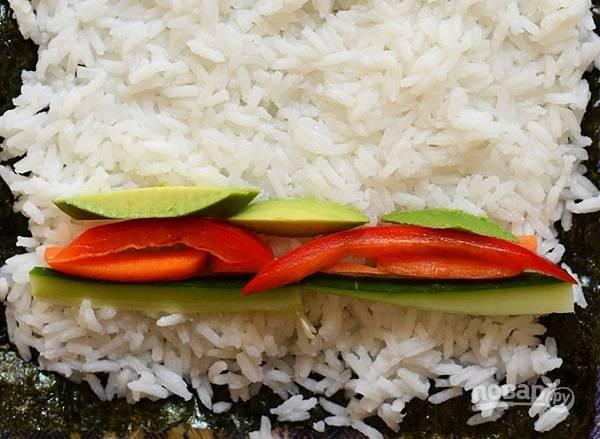 3. Подготовьте коврик (если нет, можно взять просто чистое полотенце) и застелите его пищевой пленкой. Выложите лист нори и распределите тонким слоем рис, чуть не доходя до края. Выложите овощную начинку.