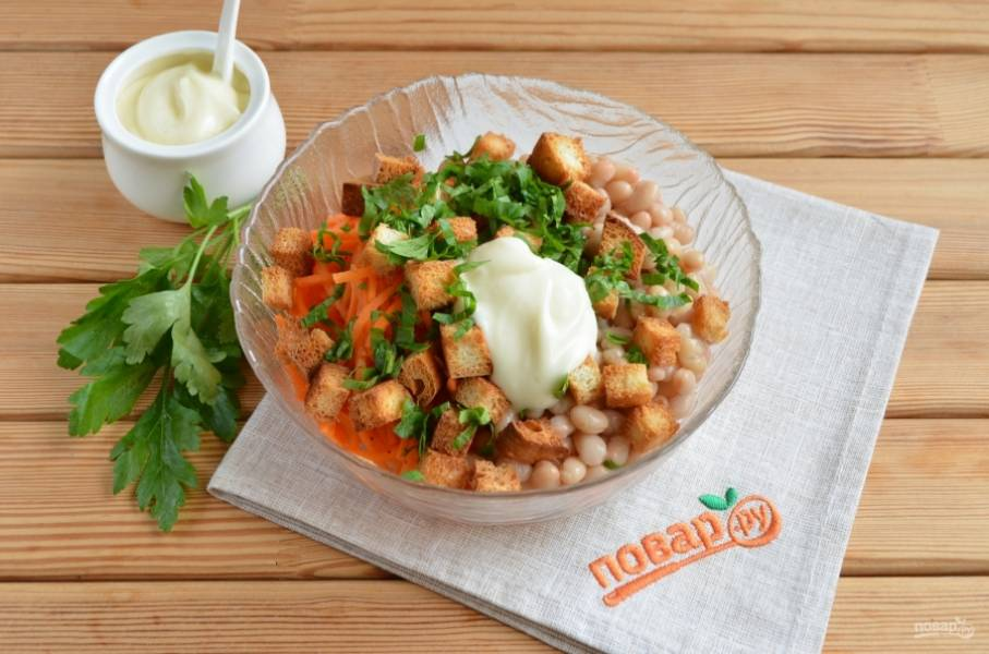 2. В салатнике соедините морковь по-корейский, фасоль, кириешки, майонез и порезанную петрушку.
