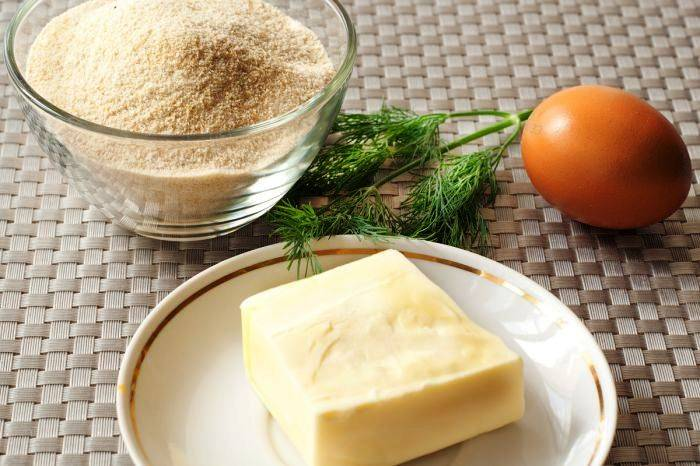 Подготовьте панировочные сухари, кляр из взбитого со щепоткой соли и перца яйца, а также начинку для котлет из замороженного сливочного масла и измельченной зелени.